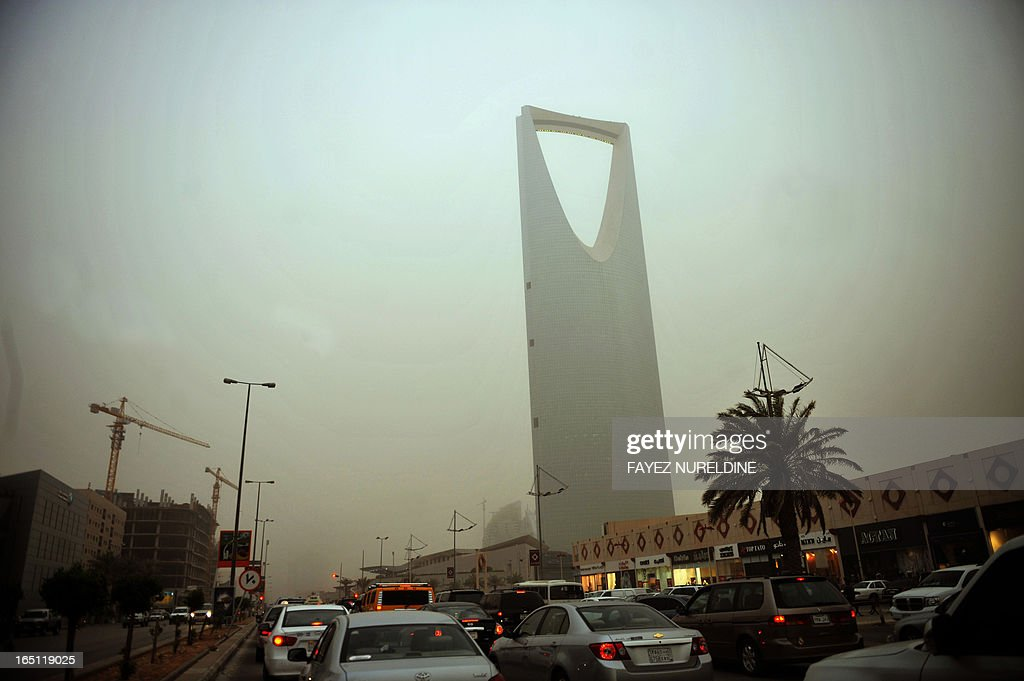 Cars drive past Kingdom Tower amid a sand storm in Riyadh on June 17 2011 as a number of Saudi women drove cars in response to calls for nationwide...