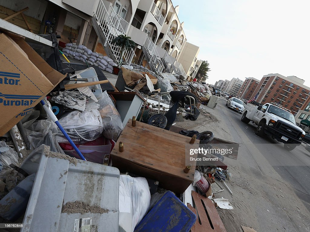 Cars drive past piled up garbage on West Broadway on November 20, 2012 in Long Beach, New York. More than three weeks after Superstorm Sandy hit the New York area, residents continue their restoration efforts in many affected areas on Long Island.