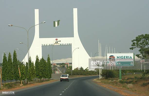 Cars drive past the city gate in Abuja Nigeria Monday December 11 2006 OPEC the producer of 40 percent of the world's oil convenes this week in Abuja...