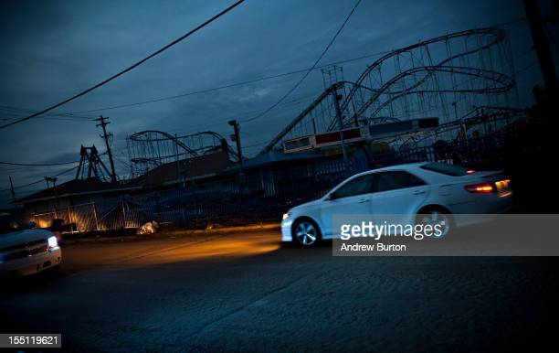 Cars drive past the remains of the Keansburg Amusement Park after Superstorm Sandy swept across the region on November 1 2012 in Keansburg New Jersey...