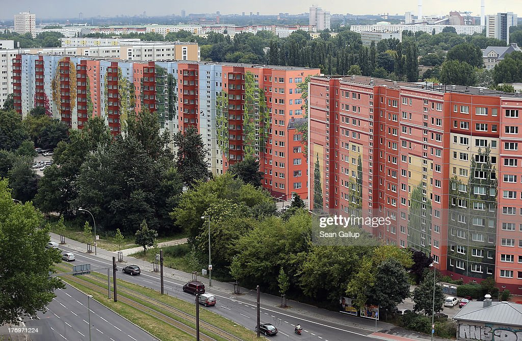 Cars drive past the Wohngenossenschaft Soldaritaet coop apartment buildings that are decorated with a 22,000 square meter mural on August 20, 2013 in Berlin, Germany. A group of artists working for French-based Citecreation painted the facades of the three buildings in imagery inspired by a nearby zoo and in cooperation with the buildings' residents. Citecreation has applied to the Guiness Book of World Records that the mural, which will be officially inaugurated on August 22, be considered as the largest mural on an inhabited building in the world.