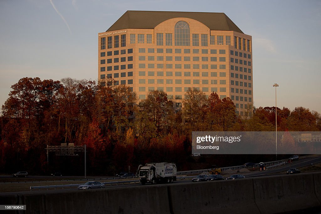 Cars drive past trees in front of of the Northrop Grumman Corp. headquarters in Falls Church, Virginia, U.S., on Friday, Nov. 16, 2012. President Barack Obama expressed confidence that he and Congress would reach an agreement that will avoid the automatic spending cuts and tax increases that are scheduled to occur at the end of the year. The fiscal cliff is the $607 billion combination of automatic spending cuts and tax increases scheduled to take effect in January. Lawmakers are trying to avert the cliff to prevent a short-term shock to the economy and reach an agreement on long-term deficit reduction. Photographer: Andrew Harrer/Bloomberg via Getty Images