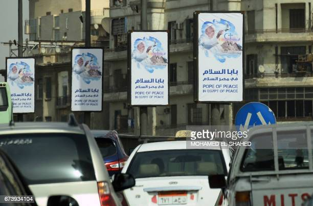 Cars drive past welcome banners bearing a portrait of Pope Francis a day ahead of his visit to the capital Cairo on April 27 2017 Pope Francis is...