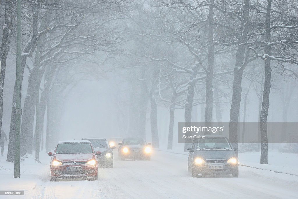 Cars drive slowly on snow-covered streets during a heavy snowfall in Zehlendorf district on December 9, 2012 in Berlin, Germany. Northeastern Germany was inundated with snow that covered highways and blanketed the region.