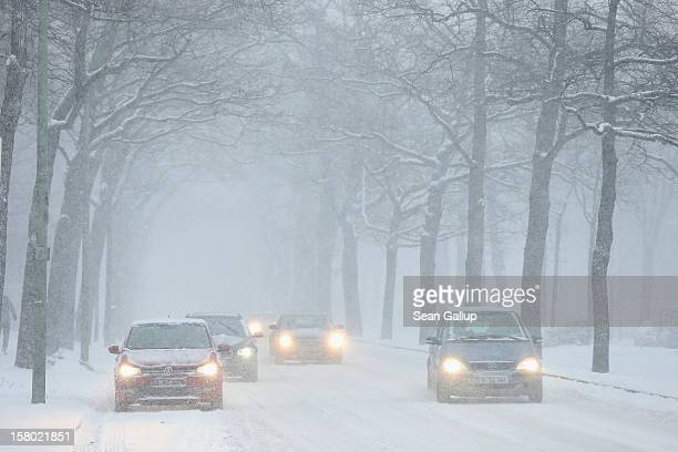 Cars drive slowly on snowcovered streets during a heavy snowfall in Zehlendorf district on December 9 2012 in Berlin Germany Northeastern Germany was...