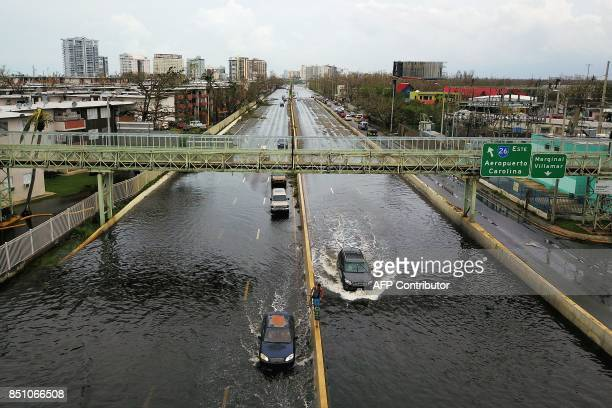 TOPSHOT Cars drive through a flooded road in the aftermath of Hurricane Maria in San Juan Puerto Rico on September 21 2017 Puerto Rico braced for...