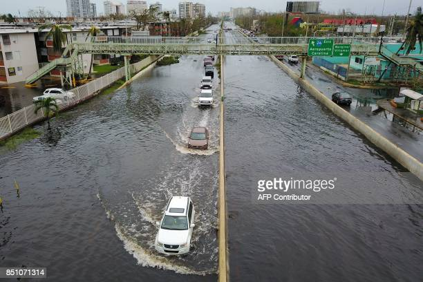 Cars drive through a flooded road in the aftermath of Hurricane Maria in San Juan Puerto Rico on September 21 2017 Puerto Rico braced for potentially...