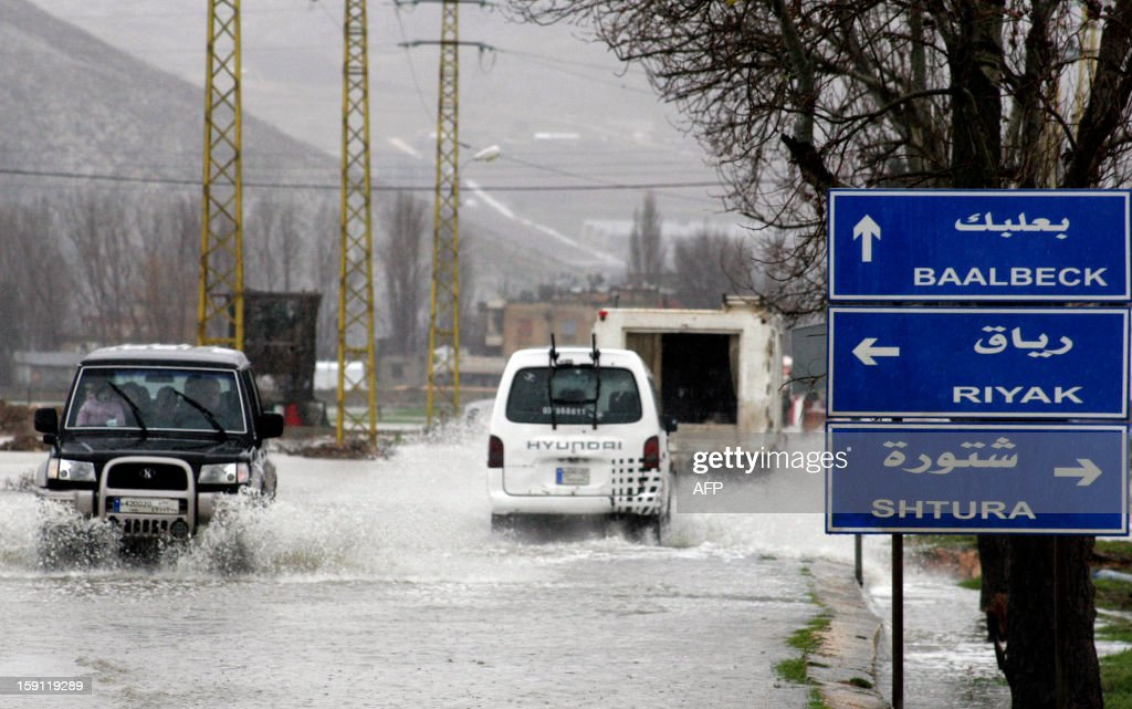 Cars drive through flood waters along the main highway that runs the length of the Bekaa Valley in eastern Lebanon, on January 8, 2013, as stormy weather sparked widespread flooding, prompting chaos on the roads and a nationwide school closure for the next two days.