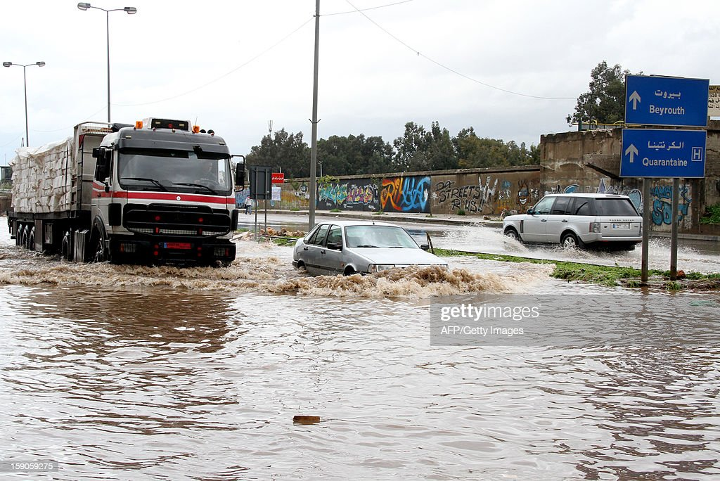 Cars drive through flood waters at the entrance of the Lebanese capital Beirut, on January 7, 2013, following a night of high winds and heavy rain fall.