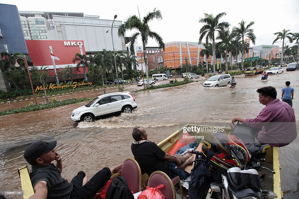 Cars drive through floodwaters in front of the Mal Kelapa Gading shopping mall in Jakarta, Indonesia, on Friday, Jan. 18, 2013. Indonesia declared a state of emergency in Jakarta as flooding brought traffic to a standstill in the city of 9.6 million people and swamped the offices of President Susilo Bambang Yudhoyono. Photographer: Dimas Ardian/Bloomberg via Getty Images