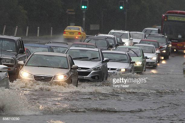 Cars drive through floodwaters on the New South Wales Central Coast on June 5 2016 in Sydney Australia The Bureau of Meteorology is forecasting up to...