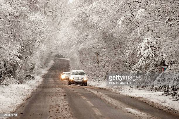 Cars drive through heavy snow in Tunbridge Wells Kent on January 6 2010 Britain braced for more transport chaos Wednesday as heavy snow and freezing...