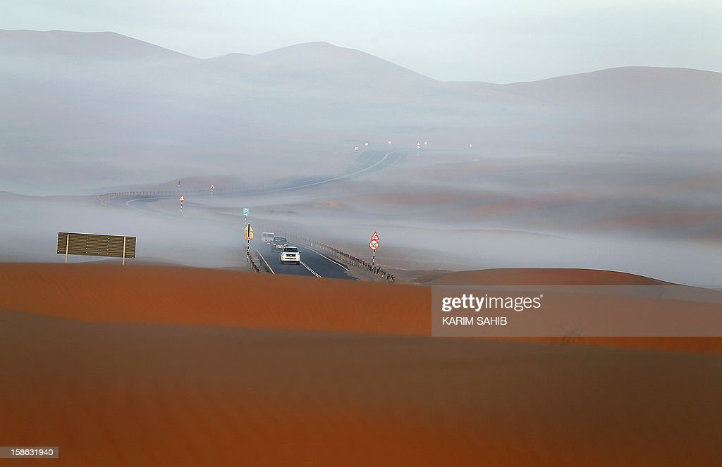 Cars drive through the Liwa desert, 220 kms west of Abu Dhabi, on the sidelines of the Mazayin Dhafra Camel Festival on December 22, 2012. The festival, which attracts participants from around the Gulf region, includes a camel beauty contest, a display of UAE handcrafts and other activities aimed at promoting the country's folklore.