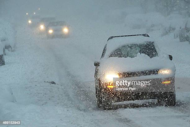 Cars drive through the snow on February 13 2014 in the Brooklyn borough of New York City In what is turning out to be one of the snowiest winter's in...