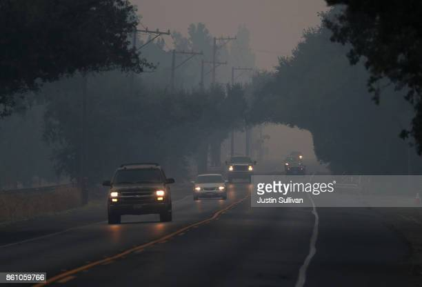 Cars drive through thick smoke along Route 29 on October 13 2017 in Yountville California At least thirty one people have died in wildfires that have...