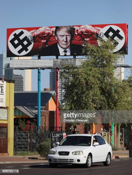Cars drives past an antiTrump billboard displaying swastikalike dollar signs near the corner of Grand Ave and Taylor Street on March 21 2017 in...