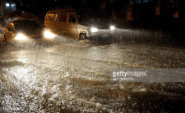 Cars drives through heavy rain and floodwater in Manila on June 17 2013 The Philippine Atmospheric Geophysical and Astronomical Services...