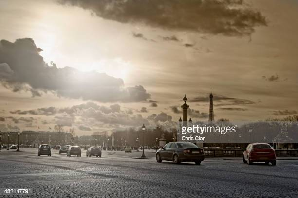 Cars driving on city street, Paris, France