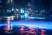 Cars driving on wet road in the rain and colored lights reflected on the wet asphalt road