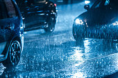 Cars driving on wet road in the rain with headlights