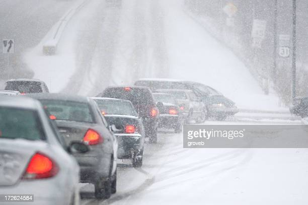 Cars driving through dangerous conditions in the snow