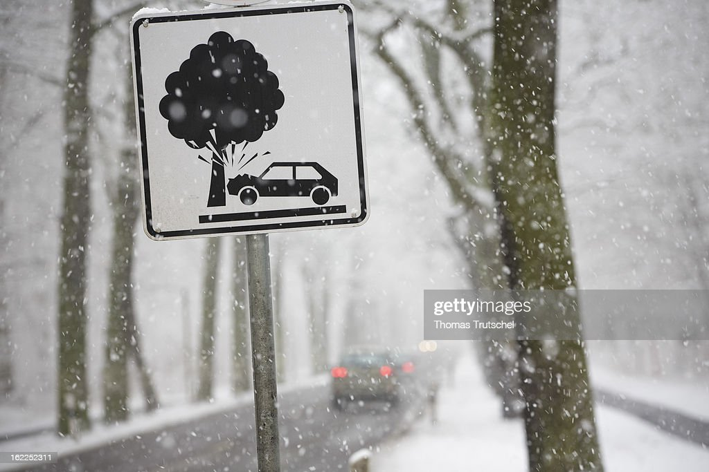 Cars driving through the snow along a tree-lined country highway on February 08, 2013 in Potsdam, Germany.