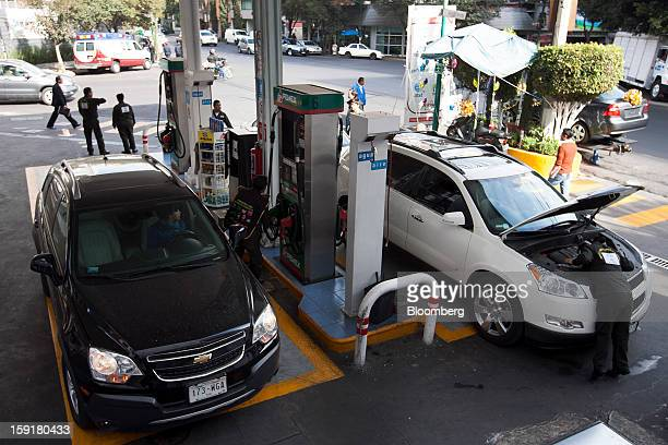 Cars get their tanks filled with gasoline at a Pemex station in Mexico City Mexico on Tuesday Jan 8 2013 Mexico's government is speeding up the...