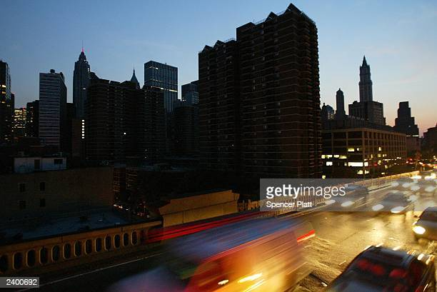 Cars head over the Brooklyn Bridge beside a blacked out New York City skyline August 14 2003 during a power outage Power went out across the East...