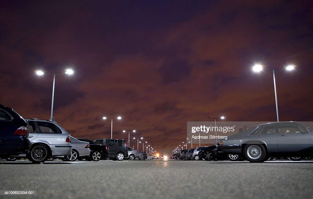 Cars in parking lot at night (surface level) : Stock Photo