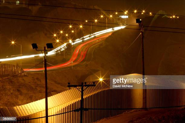Cars in Tijuana Mexico drive parallel multiple fences on the US side of the border with Mexico that creates a barrier against illegal border crossers...