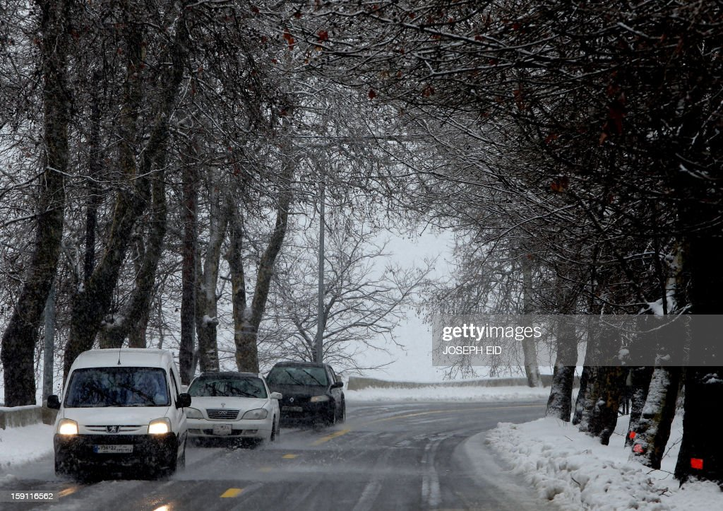 Cars make their way through a snowy road near the mountain village of Sawfar on January 8, 2013. Stormy weather, including high winds and heavy rainfall, lashed the eastern Mediterranean coast, downing power lines and trees and causing several injuries in a number of countries.