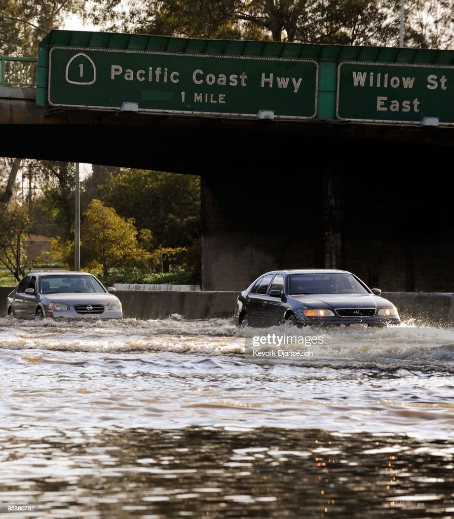 Cars make their way through the flooded north and southbound lanes of 710 Long Beach Freeway the main artery to Long Beach and Los Angeles ports on...