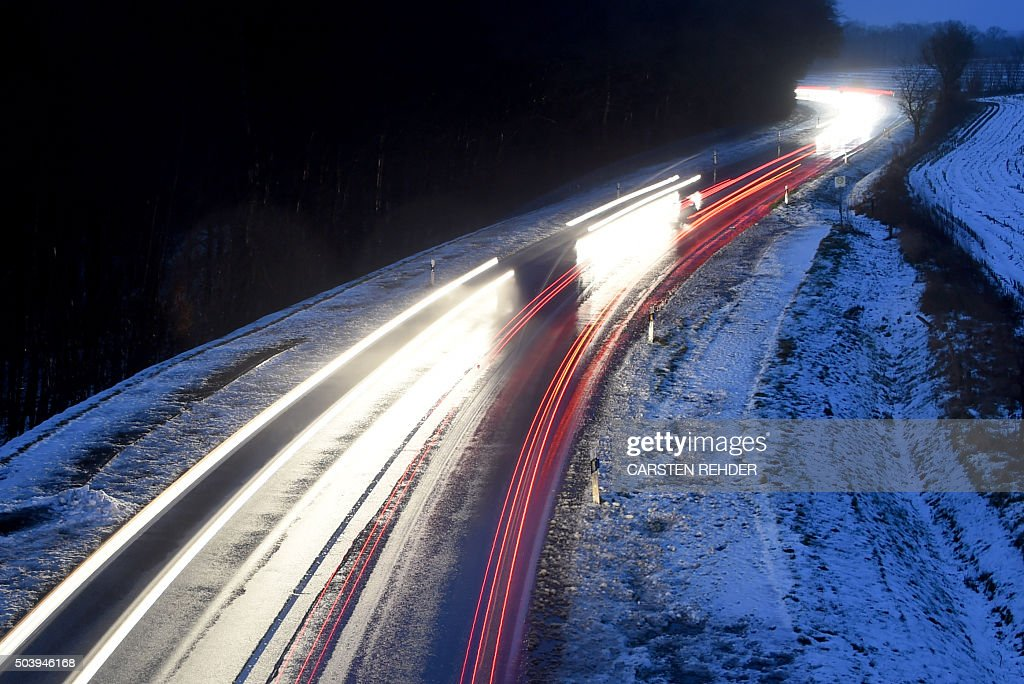 Cars make their way through the snowy B430 national road near Aukrug close to Neumuenster northwestern Germany after heavy snowfall on January 8 2016...