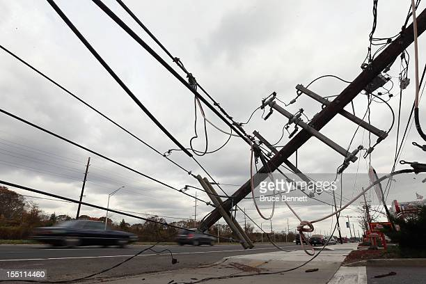 Cars move past downed power wires on Sunrise Highway on November 1 2012 in Massapequa Park New York Superstorm Sandy which has left millions without...