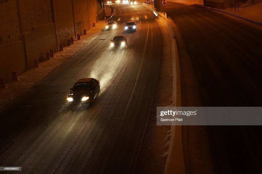 Cars move slowly down a highway during a snow storm on December 14, 2013 in the Brooklyn borough of New York, United States. Much of the Northeast was hit Saturday by a storm stretching over 1,000 miles that could result in at least a foot of snow on parts of New England.