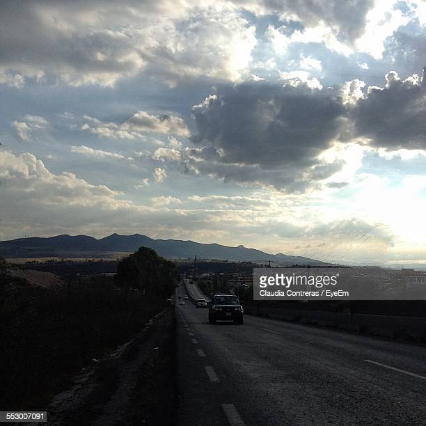 Cars Moving On Road Against Cloudy Sky