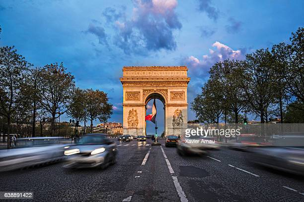 Cars moving on road at Arc de Triomphe against sky