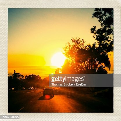 Cars Moving On Road At Sunset