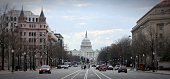 Cars Moving On Road Leading Towards United States Capitol Against Sky In City