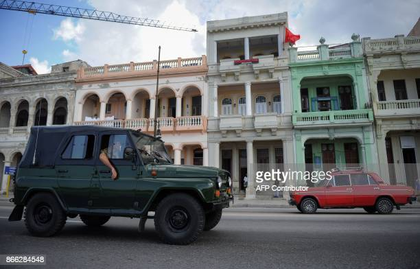 Cars of Soviet origin pass by the retroSoviet restaurant Nazdarovie in Havana on October 16 2017 With three decades of close alliance with the Soviet...