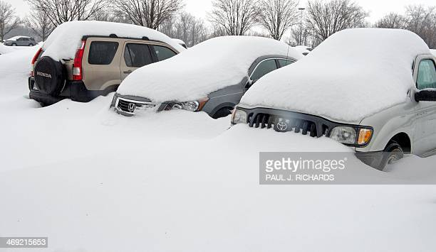 Cars of travelers are covered in deep snow February 13 2014 at the long term parking lot at Dulles International Airport in Virginia near Washington...