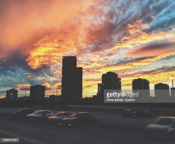 Cars On City Street Against Cloudy Sky At Sunset