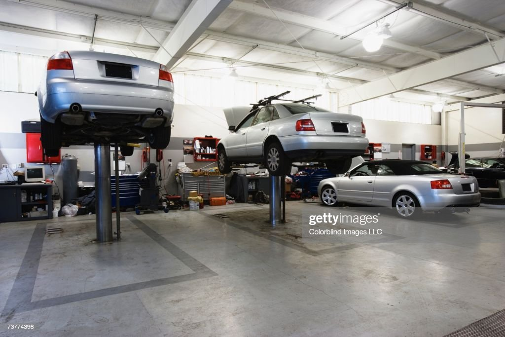 Cars on hydraulic lifts at auto repair shop