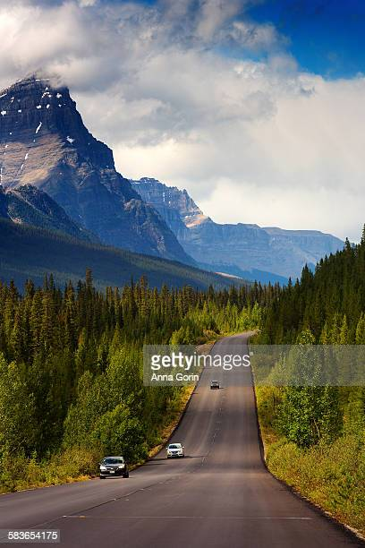Cars on Icefields parkway with mountains behind