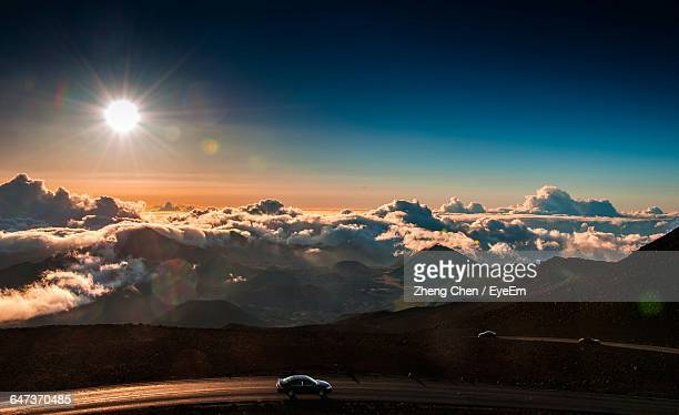 Cars On Mountain Road Against Cloudy Sky