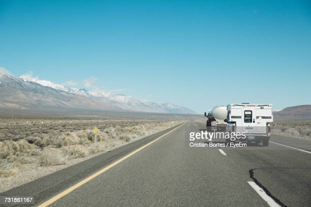 Cars On Road In Desert Against Clear Sky