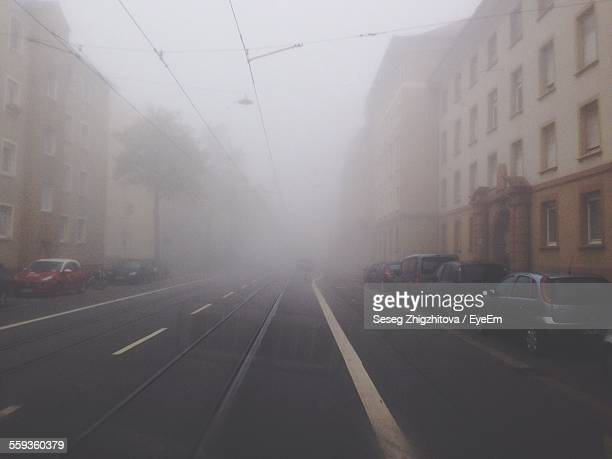 Cars On Street Amidst Buildings In City During Foggy Weather