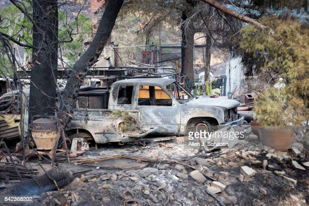 Cars parked in front of a home and property lies in ruin as it was one of three homes and a shed were destroyed in the the La Tuna Canyon fire along...