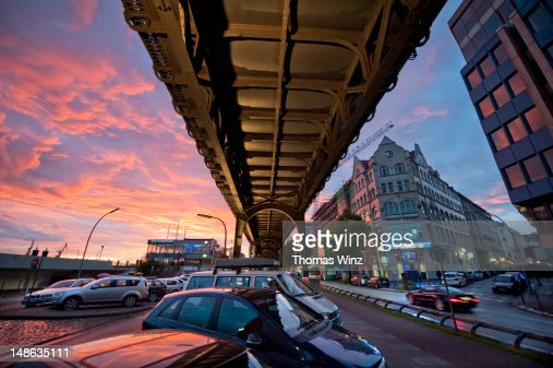 Cars parked under train overpass near Landungsbruecken at dusk. : Stock Photo
