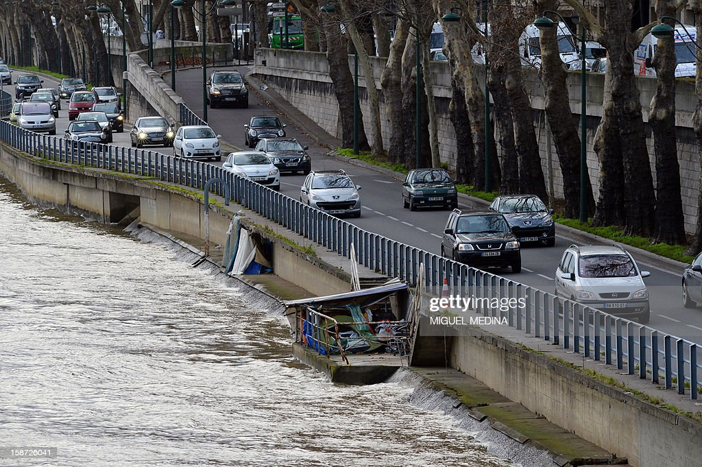 Cars pass a shanty house in Paris on December 26, 2012. AFP PHOTO / Miguel Medina